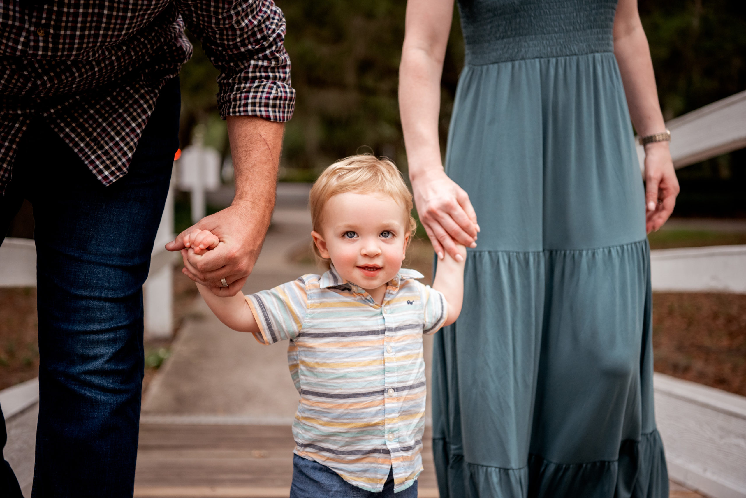 Little boy holding mom and dads hands